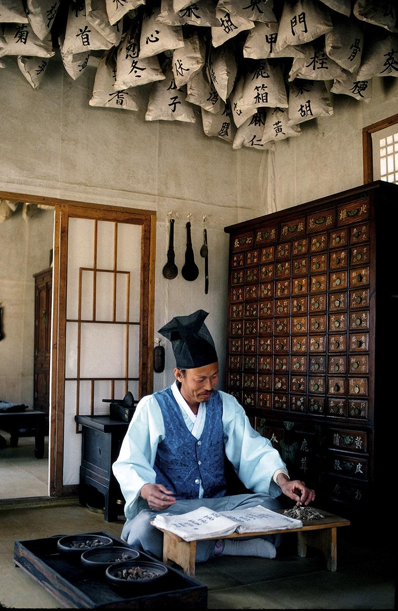 Pharmazie / Apotheker. - Traditioneller koreanischer Apotheker in der Apotheke im Koreanischen Museumsdorf Suwon (Gyeonggi-do, S¸dkorea). - Foto, 1980.