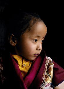521. The young incarnation of the great Tibetan master Dilgo Khyentse Rinpoche (1910-1991), Orgyen Tendzin Jigme Lhundrup, at his window, watching the annual festival of sacred dances at his monastery, Shechen, in Nepal. 1997 Orguièn Tendzin Jigmé Lhündroup (Détenteur Spontané et Impavide des Enseignements de Padmasambhava), l'incarnation de Dilgo Khyentsé Rinpotché (1910-1991), contemplant le festival annuel de danses sacrées, à son monastère de Shéchèn, au Népal. 1997