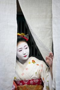 A maiko geisha looks out from behind the traditional noren curtain of a residence in the Kitano district of Kyoto, Japan.